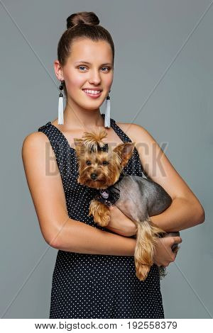 Beautiful young teenage girl in dress holding small cute yorkshire terrier dog. Copy space. Studio shot on grey background.