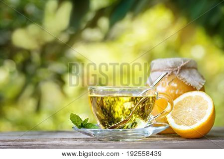 mint tea, honey and lemon on wooden table with blurred green natural background. Glass cup of herbal tea. Still life healthy products for treatment flu. Alternative medicine concept