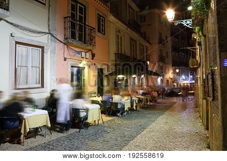 Night view of the narrow streets of old Lisbon with cafe outdoors Portugal