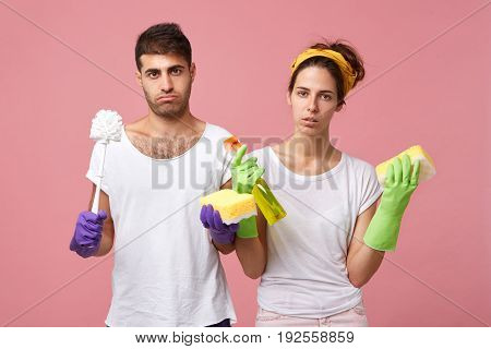 Upset Tired Young Husband And Wife In Protective Rubber Gloves While Tidying New Apartment After Rep