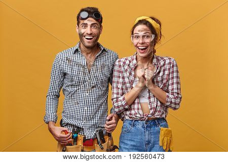 Attractive Man And Woman Maintenance Workers, Technicians, Electricians, Plumbers Or Mechanics Cheer