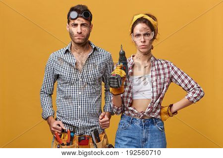Indoor Shot Of Confident Young Maintenance Workers Or Repairmen In Overalls, Protective Wear, Standi