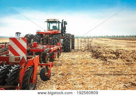 Red tractor working in a field on a bright sunny day. The concept of work in a fields and agriculture industry.
