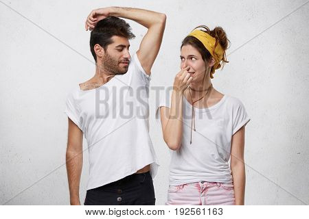 Female Having Disgusted Look Covering Her Nose With Hand While Smelling Her Husband`s Armpit. Bearde