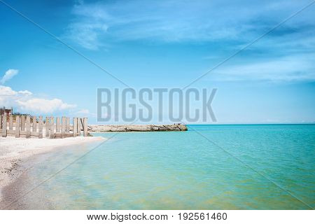 Beach of the sea coast with white sand and blue sky on a clear day.