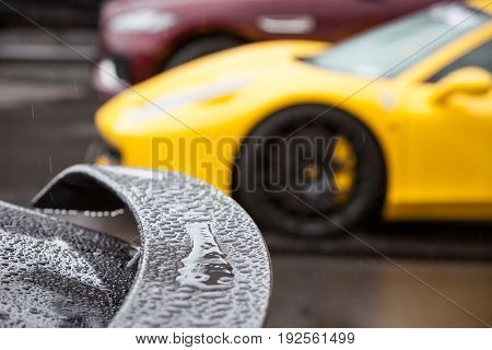 Rain drops on the spoiler of a sports car compared to other cars