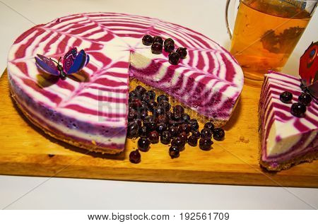 beautiful bright cake with currants, white with purple cake adorned with berries, cut