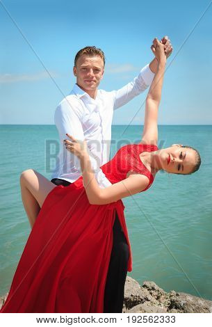 Man and woman posing in dance by the sea on a bright sunny day.