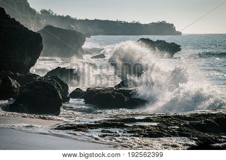 Ocean waves crashing onto the rocks in the sunset. Indonesia Bali