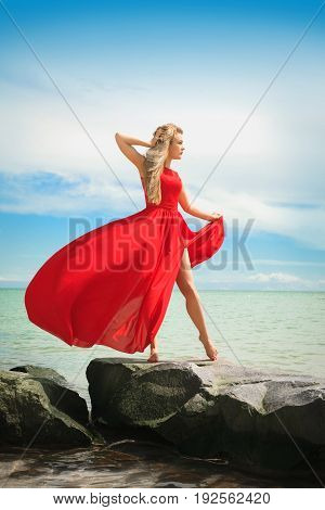 Beautiful woman in a bright red dress by the sea on a sunny summer day.
