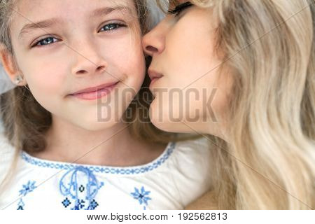 Mother kisses her little daughter. Close-up portrait.