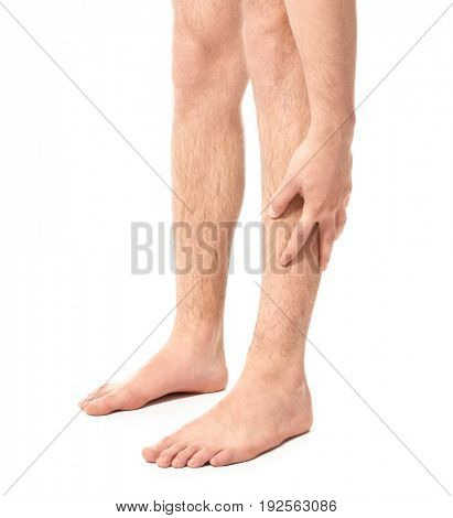 Young man suffering from pain in leg on white background
