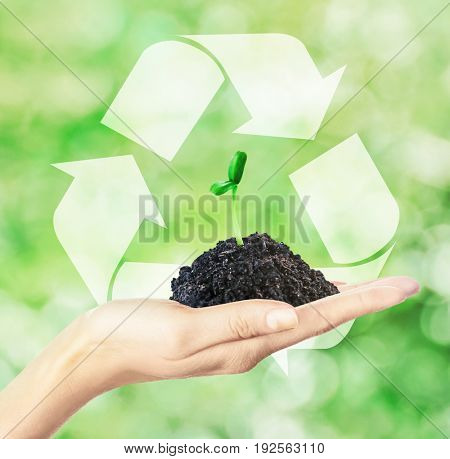 Concept of environmental conservation and protection. Woman holding soil with seedling and symbol of recycling on background