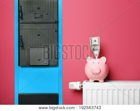 Energy savings concept. Solid fuel boiler, radiator with piggy bank and money on color background