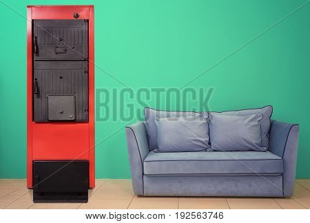 Energy savings concept. Solid fuel boiler and couch on color wall background