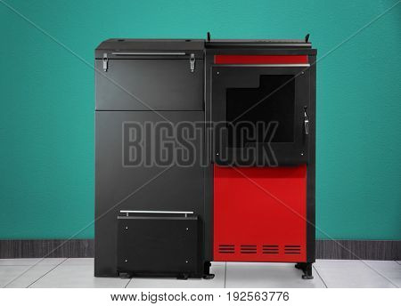 Energy savings concept. Solid fuel boiler on color wall background