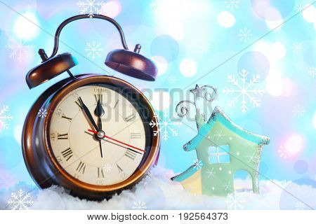 Countdown to holiday celebration. Alarm clock and Christmas decoration on color background