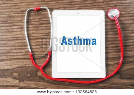 Health care concept. Stethoscope and tablet with word ASTHMA on screen, wooden background