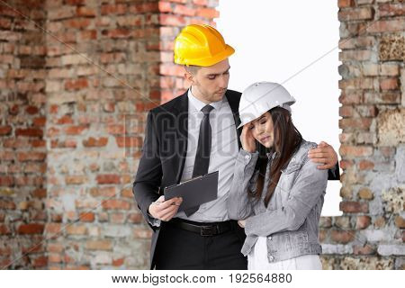 Insurance adjuster and young woman in abandoned building