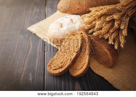 Fresh bread and wheat on the dark wooden table.