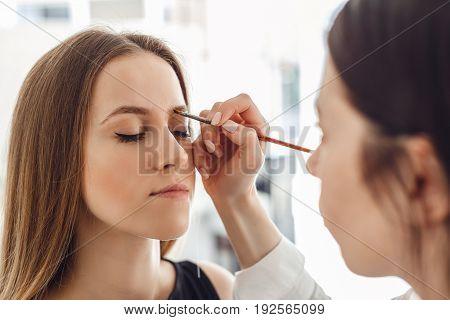 Beautiful young woman gets eyebrow correction procedure. Young woman tweezing her eyebrows in beauty saloon.