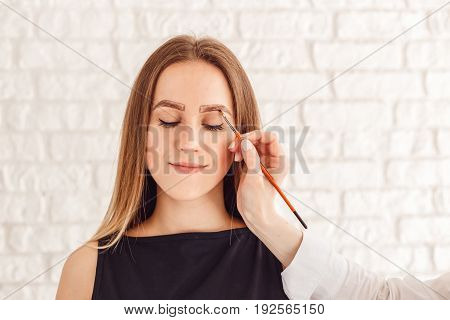 Eyebrow correction procedure for the smiling model with long eyelashes. Beautiful young woman gets eyebrow correction procedure.