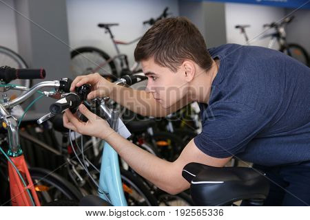 Young man checking bicycle brake system in shop