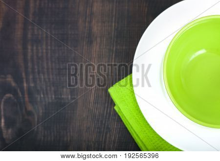 Empty plate and towel over wooden table background. Top view with copy space