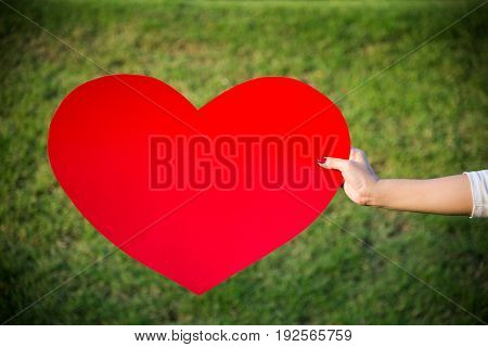 Big red heart as copy space for text decoration design in asian woman hand holding over green garden for Valentines day concept