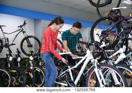 Smiling girl showing bicycle to young man in shop