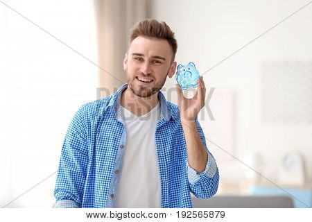 Happy young man holding piggy bank on blurred background