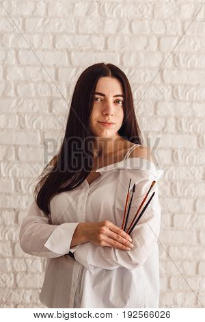 Beautiful young beautician woman holding set of make up brushes in saloon