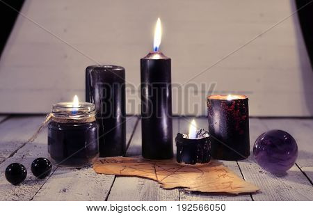 Black candles, old parchment and magic ball against white planks background. Halloween concept. Mystic background with occult and magic objects on witch table