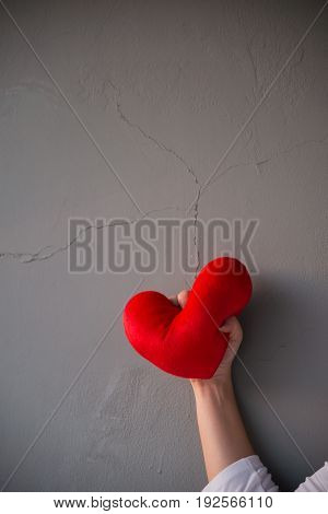 Red heart pillow was squeezed angrily over cracked grey wall background showing fail love on Valentines day occasion
