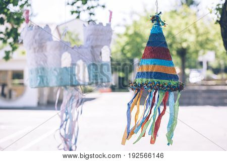 Multi colored castle and cone shaped pinatas