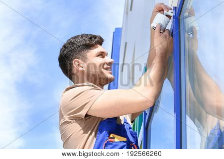 Electrician fixing video surveillance camera outdoors