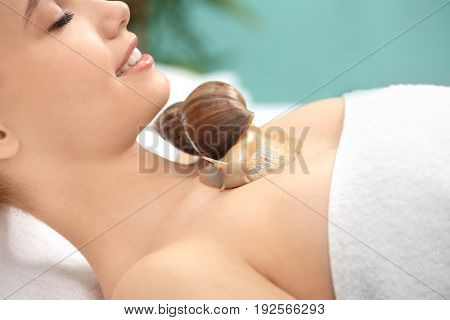 Young woman undergoing treatment with giant Achatina snail in beauty salon, closeup