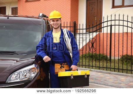 Smiling young electrician with bunch of wires and toolbox standing near car outdoors