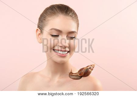 Beautiful young woman with giant Achatina snail on light background