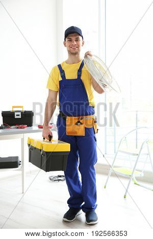 Young electrician with tools and wires at workplace