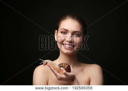 Beautiful young woman with giant Achatina snail on dark background
