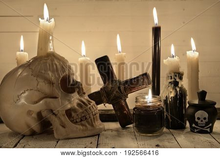 Scary still life with skull, burning candles and cross. Halloween and voodoo concept. Mystic background with occult and magic objects on witch table
