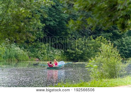 Moscow Russia June 16 2013: Family idyll. A family of three people is swimming on a boat. Poplar fluff lies on the surface of the water. Silver-grape pond.
