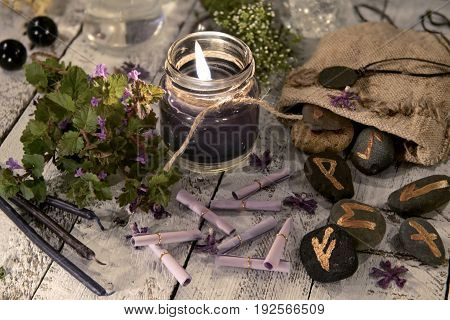 Fortune telling still life with black candle, runes and wish scroll. Halloween and astrology concept. Mystic background with occult and magic objects on witch table