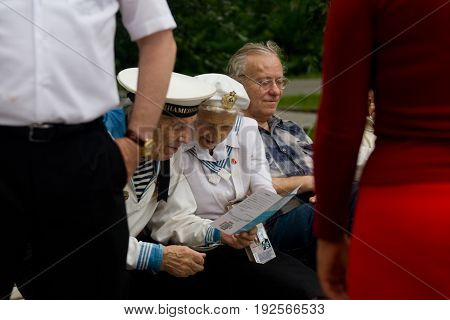 Moscow Russia. July 28 2013: Elderly people in the uniform of the Navy are reviewing the booklet. Izmailovsky Park.
