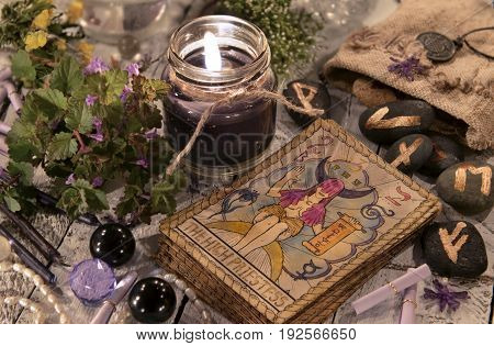 Black candle with the tarot cards and runes. Halloween and fortune telling concept. Mystic background with occult and magic objects on witch table