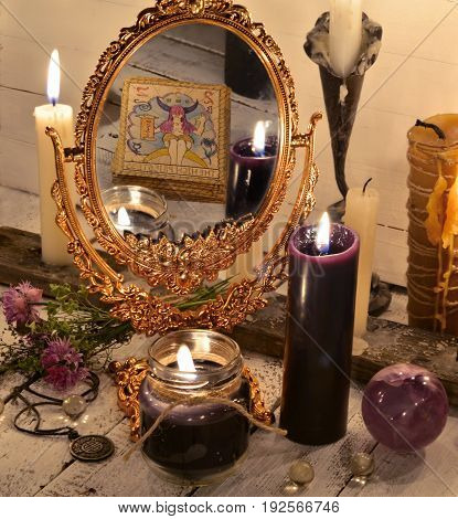 Close up with magic mirror and black candles. Fortune telling and halloween concept. Mystic background with occult and magic objects on witch table