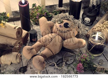 Scary voodoo doll with paper scrolls and black candles. Halloween concept. Mystic background with occult and magic objects on witch table