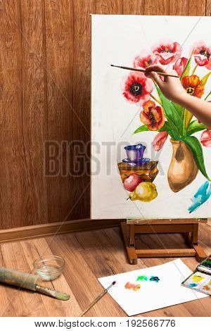 Process of drawing watercolor flowers. Unrecognizable artist's hand paints bouquet picture . Drawing lessons, art school, young artist, painter workplace concept