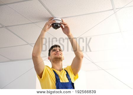 Electrician fixing video surveillance camera indoors